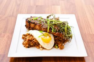 COM SUON NUONG Gunthorp farm grilled lemongrass pork chop, local baby greens, fried egg, pickled watermelon, dirty rice